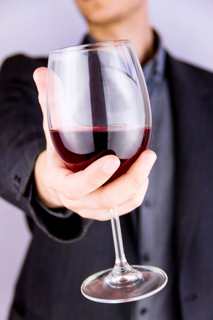 Close-up shooting of mans hand holding a glass of wine