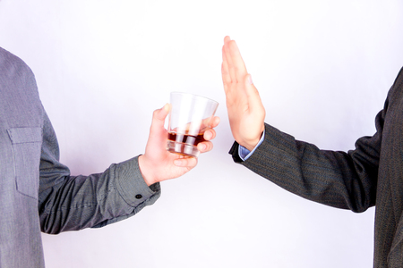Close-up of businessman hand rejecting glass of whisky offered by businessperson Stockfoto