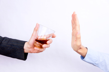 Close-up of businessman hand rejecting glass of whisky offered by businessperson 스톡 콘텐츠