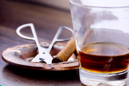 Close-up shooting of glass shot with cognac, cigar cutter, ashtray and cuban cigar Stock Photo