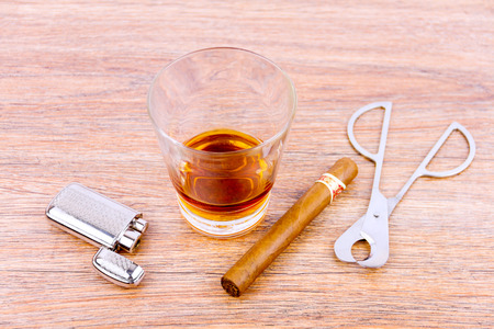 Close-up shooting of glass shot with cognac, cigar cutter, lighter and cuban cigar Stock Photo