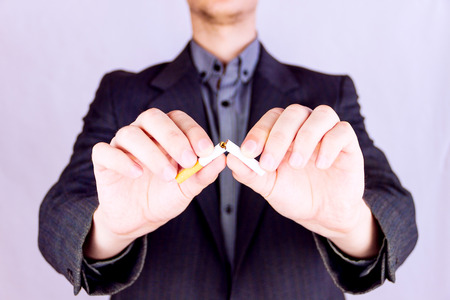Young man wearing formal clothing cutting a cigarette