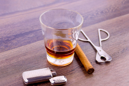 Close-up shooting of glass shot with cognac, cigar cutter, lighter and cuban cigar Stock Photo