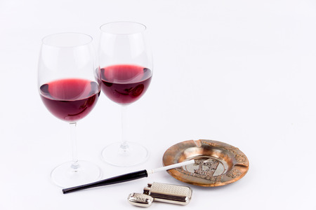Close-up shooting of a cigarette with cigar-holder, lighter, ashtray and two glasses of red wine isolated on white background
