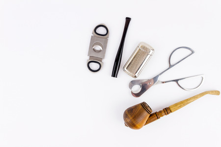 encendedores: Metal cigar cutters, lighter, cigarette-holder and  wooden pipe isolated on white background Foto de archivo
