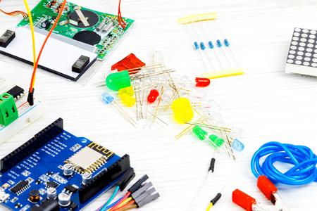 coordinacion: Microcontroladores, chips, resistencias, diodos emisores de luz y clavijas en el escritorio blanco del ingeniero de hardware. Lugar de trabajo del ingeniero
