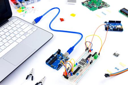マイコン チップ、抵抗器、usb ケーブル、ハードウェア エンジニアの白いデスクトップ上のノートブック。エンジニアの職場 写真素材
