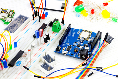 Microcontrollers, chips, resistors and light-emitting diodes on white desktop of hardware engineer. Engineer workplace Stock Photo
