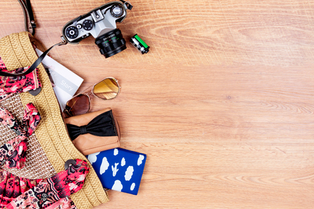 Top view of essentials for modern young person. Objects of a traveller isolated on wooden background: sunglasses, camera, summer bag, wallet, notebook, passport Stock Photo