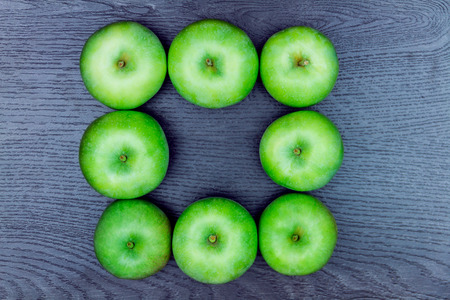 Healthy food. Square made of several apples isolated on wooden background. Stock Photo