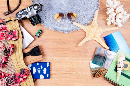 Top view of essentials for modern young person. Objects of a traveller isolated on wooden background: sunglasses, camera, hat, summer bag, wallet, notebook, passport, photos, shell, sea star and coral