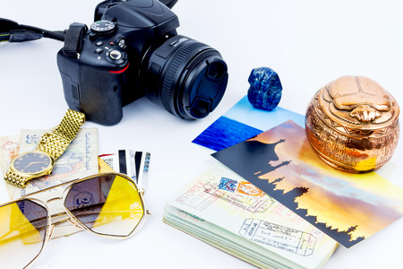 Side view of essentials for modern young person. Objects of a traveller isolated on white background: envelope , souvenir, camera, cash,  sunglasses, watch, photos of Turkey, the sea and passport with visas