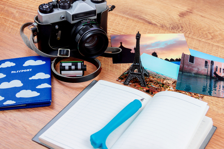 stuff: Side view of essentials for modern young person. Objects of a traveller isolated on wooden background: notebook with a pen, wallet with cash and cards, passport, film, camera,  photo and souvenirs Stock Photo