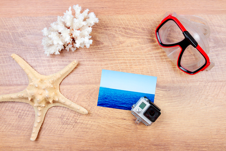 Top view of essentials for modern young person. Objects of a traveller isolated on wooden background: dive mask, go pro, coral and sea star, photo card Stock Photo
