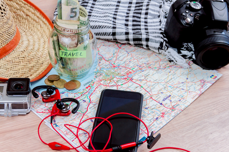 Top view of essentials for modern young person. Objects of a traveller isolated on wooden background: map with baltic countries, hat, camera, gopro, scarf, money, coins, smart phone with headphones Stock Photo