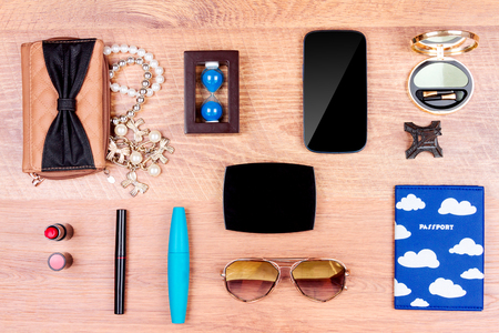 Top view of essentials for modern young person. Objects of a traveller isolated on wooden background: smartphone, passport, sunglasses, wallet, necklace,eyeliner, lipsticks and mascara, eyeshadow, mirror and souvenirs