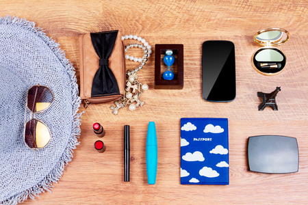 Top view of essentials for modern young person. Objects of a traveller isolated on wooden background: smartphone, passport, sunglasses, hat, wallet, necklace,eyeliner, lipsticks and mascara, eyeshadow, mirror and souvenirs Stock Photo