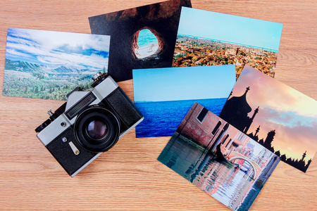 Top view of essentials of a traveller: camera and photo cards of Venice, Stambul, Carpathians and ocean