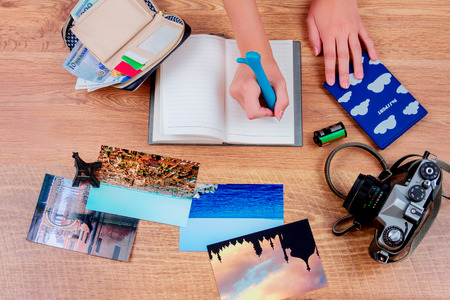 Objects of a traveller isolated on wooden background: notebook with a pen, wallet with cash and cards, passport, film, camera,  photos of turkey, italy, france  and souvenir. Top view of a girls hands making notes in the notebook