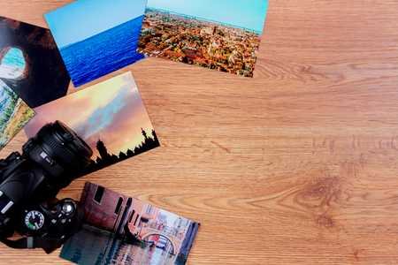 stuff: Top view of essentials of a traveller: camera and photo cards of Venice, Stambul, Carpathians and ocean