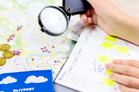 Top view of essentials for modern young person. Objects of a traveller isolated on wooden background: travel map,  passport, coins, lens,  notebook with plan for vacation . Girl planning the trip looking at the map