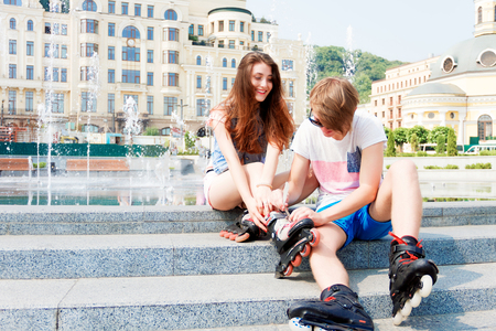 Young sporty couple in love sitting near the fountain. Guy helping his girlfriend to put on roller skates.