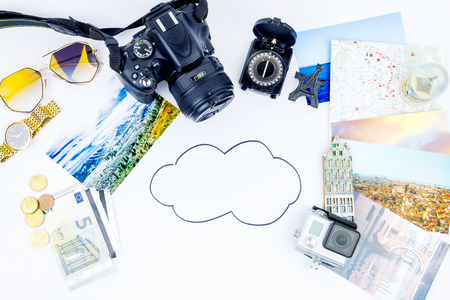 Planning of travelling concept. Top view of essentials for modern young person. Objects of a traveller isolated on white background: compass, sunglasses, go pro, map,  camera, cash,  film,  souvenirs, watch, photos of Italy, Carpathians and the sea