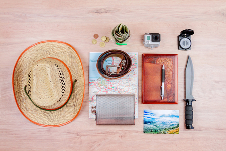Top view of essentials for modern young person. Objects of a traveller isolated on wooden background: flask, hat, leather belt,  go pro, map, money, coins, compass, knife, notebook with pen and a photo of carpathians
