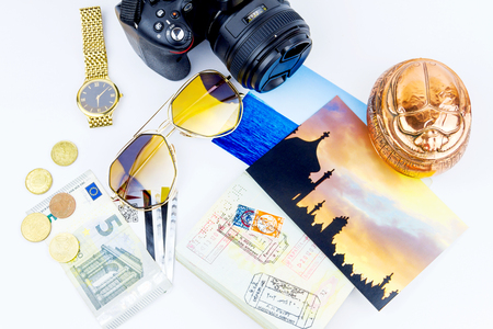Top view of essentials for modern young person. Objects of a traveller isolated on white background: envelope , souvenir, camera, cash,  sunglasses, watch, photos of Turkey and the sea and passport with visas