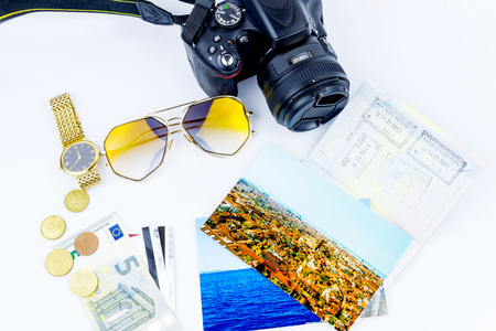 Top view of essentials for modern young person. Objects of a traveller isolated on white background: envelope ,  camera, cash,  sunglasses, watch, photos of Italy, Carpathians and the sea and passport with visas