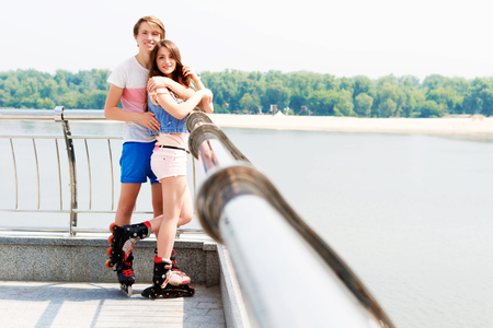 Young couple in love with roller skates hugging on the seafront