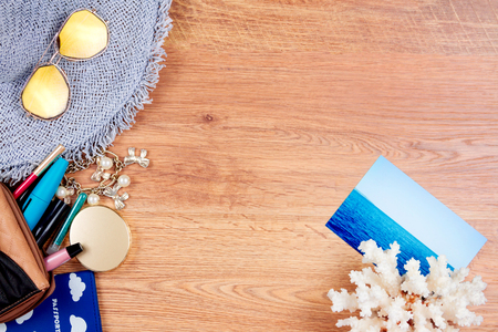 Top view of essentials for modern young person. Objects of a traveller isolated on wooden background: hat, sunglasses, passport, cosmetics (mascara, eyeliner, mirror, eyepencil), bracelet, coral and photo card Stock Photo