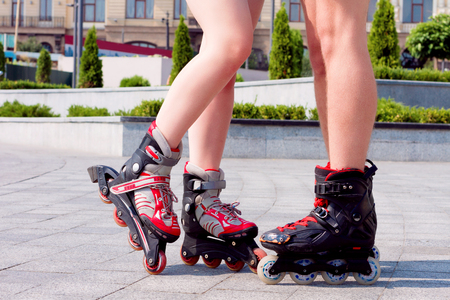 Body parts. Close up of copules legs wearing roller skates. Couple in love