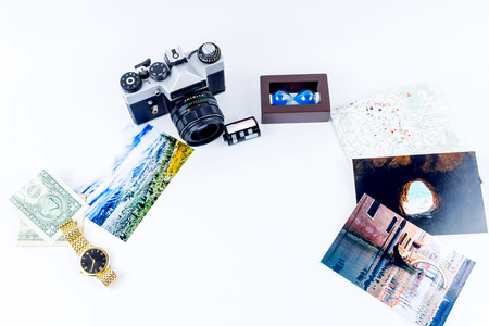 Top view of essentials for modern young person. Objects of a traveller isolated on white background: map ,  camera, cash,  film,  watch, photos of Italy, Carpathians and the sea