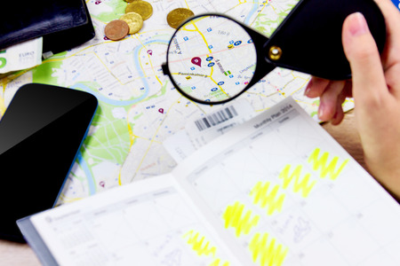 Top view of essentials for modern young person. Objects of a traveller isolated on wooden background: travel map, smart phone, wallet with cash, coins, lens,  notebook with plan for vacation . Girl planning the trip looking at the map