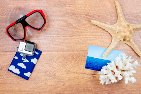 dive trip:  Top view of essentials for modern young person. Objects of a traveller isolated on wooden background: dive mask, go pro, coral and sea star, photo card and passport