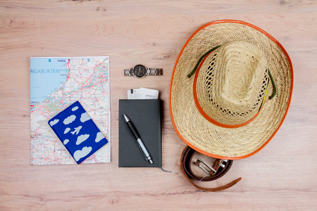 Top view of essentials for modern young person. Objects of a traveller isolated on wooden background: hat, leather belt, watch, passport, map and notebook with pen
