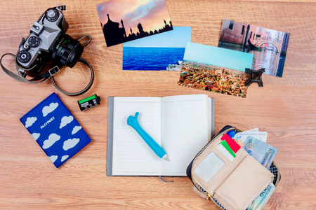Top view of essentials for modern young person. Objects of a traveller isolated on wooden background: notebook with a pen, wallet with cash and cards, passport, film, camera,  photos of turkey, italy, france  and souvenir