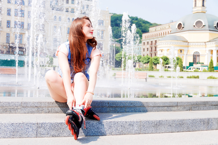 roller blade: Girl wearing roller skates sitting near the fountain and smiling