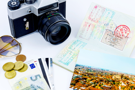 Side view of essentials for modern young person. Objects of a traveller isolated on white background: envelope , camera, cash,  sunglasses, watch, photos of italy and passport with visas
