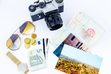 Top view of essentials for modern young person. Objects of a traveller isolated on white background: envelope , camera, cash,  sunglasses, watch, photos of italy