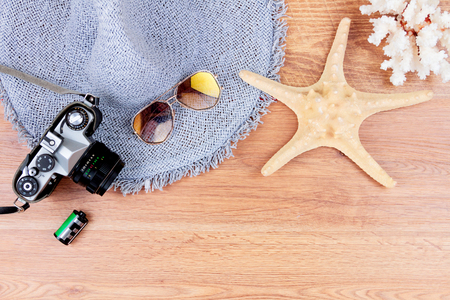 Top view of essentials for modern young person. Objects of a traveller isolated on wooden background: sunglasses, camera, hat, film, sea star and coral