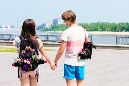 Young sporty couple in love walking along the promenade with roller skates and rucksack decorated with colorful badges and toys.  Stock Photo
