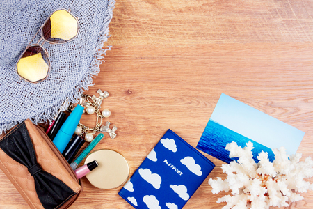 Top view of essentials for modern young person. Objects of a traveller isolated on wooden background: hat, sunglasses, passport, cosmetics (mascara, eyeliner, mirror, eyepencil), mirror, bracelet, coral and photo card