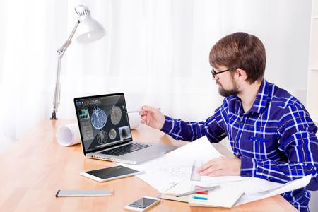 Cad Ingenieur Arbeitsplatz mit Laptop, Zeichnungen, Notizblock und Stift, Smartphone und Lampe. Junge Ingenieur entwickelt neue 3D-Modell der Turbine für die Schwerindustrie Standard-Bild