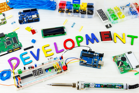 Microcontrollers, chips, resistors and light-emitting diodes on white desktop of hardware engineer. Colorful letters connected together to word development