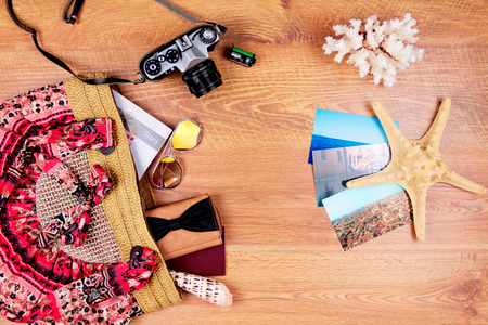 Top view of essentials for modern young person. Objects of a traveller isolated on wooden background: sunglasses, camera, film, summer bag, wallet, notebook, passport, photos, sea star and coral