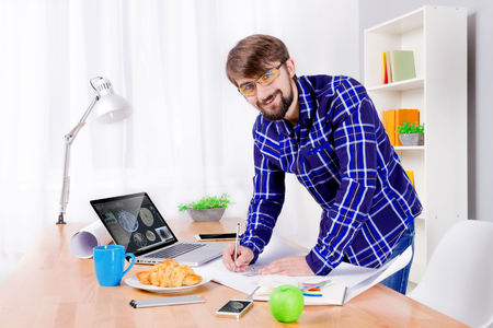 Cad engineers workplace with laptop, drawings, notepad and pen, smartphone, apple, croissant, blue cup and lamp. Young engineer developing new 3d model of turbine for heavy industry  Stock Photo