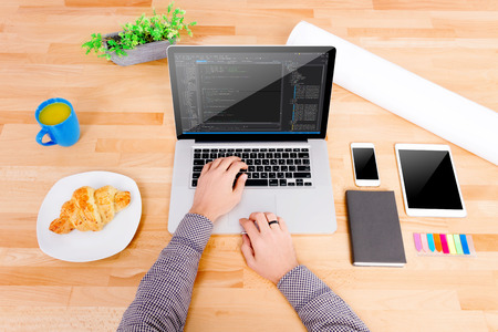 Software engineer's workplace with laptop, tablet, mockup smartphone, blue cup, croissant. The engineer working on the laptop. Note: Code was got from github with free license for commercial use (MIT)