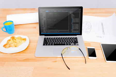 Software engineers workplace with notebook, mockup tablet, glasses, sketching,mockup smartphone, blue cup, croissant. Note: Code was got from github with free license for commercial use (MIT)